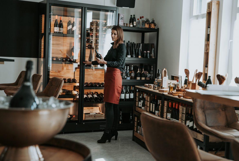 Eine Frau steht vor dem Weinkühlschrank und hält eine Weinflasche in der Hand.