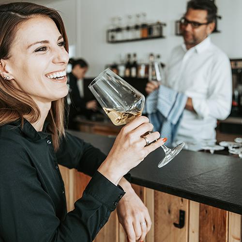 Frau lächelt und hält ein Weinglas in der Hand.