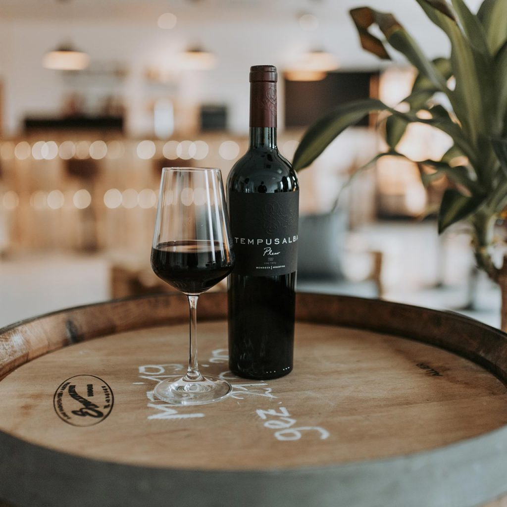 Eine Flasche Rotwein steht auf einem Fass.